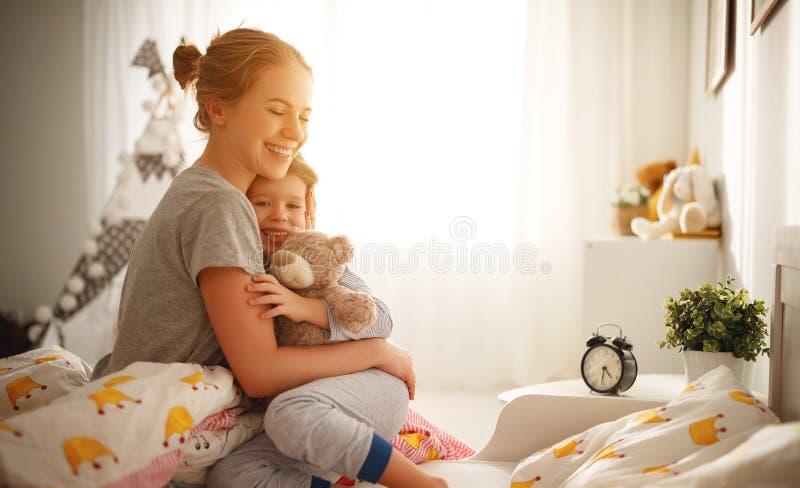Matka budzi się jej córki w łóżku w ranku obraz royalty free