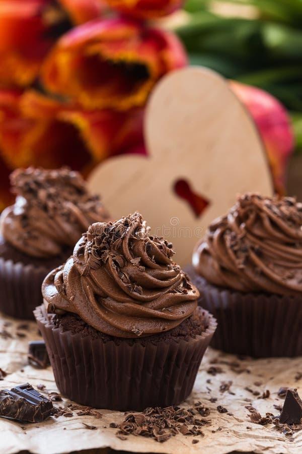 Matka dnia czekoladowe babeczki z wiosna tulipanami i drewnianym h zdjęcia stock