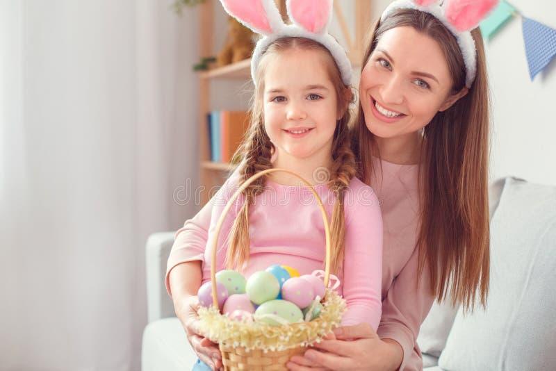 Matka i córka w królików ucho wpólnie w domu Easter świętowaniu siedzi przyglądającego kamery mienia kosz z jajkami fotografia stock