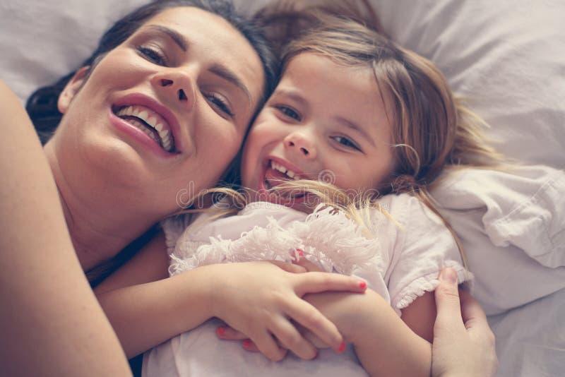 Matka i córka bawić się w łóżku fotografia royalty free