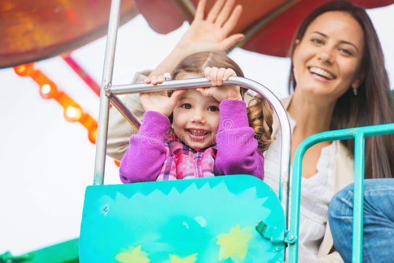 Matka i córka cieszy się zabawa jarmark jedziemy, park rozrywki fotografia stock