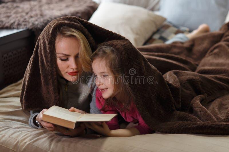 Matka i córka kłamamy na łóżku pod koc i czytamy książkę fotografia stock