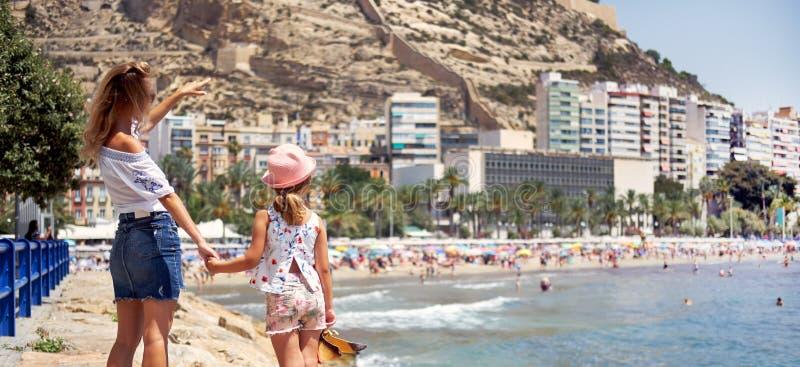Matka i córka na Postiguet wyrzucać na brzeg przy latem, tylni widok Macierzysty seans Santa Barbara kasztel zdjęcia royalty free