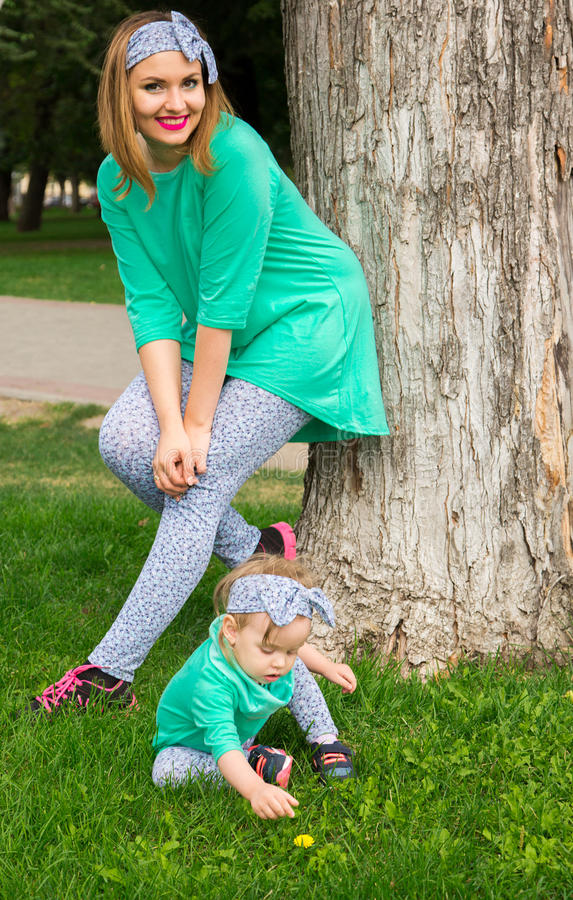 Matka i córka pozuje na trawie zdjęcie stock