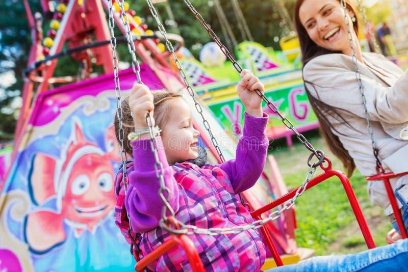 Matka i córka przy zabawa jarmarkiem, łańcuch huśtawki przejażdżka fotografia royalty free