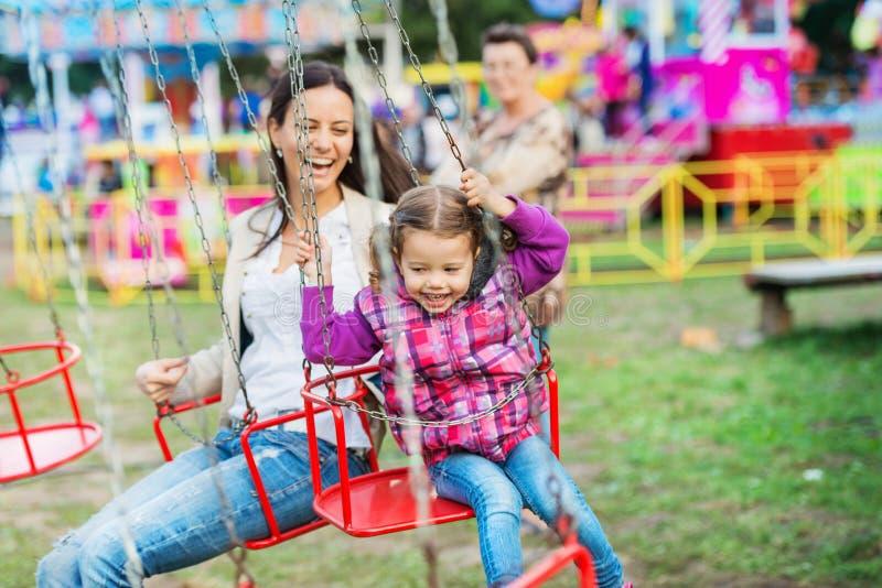 Matka i córka przy zabawa jarmarkiem, łańcuch huśtawki przejażdżka fotografia stock
