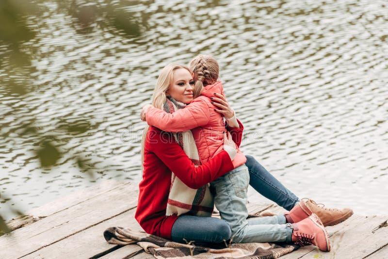 Matka i córka siedzi blisko jeziora zdjęcie stock
