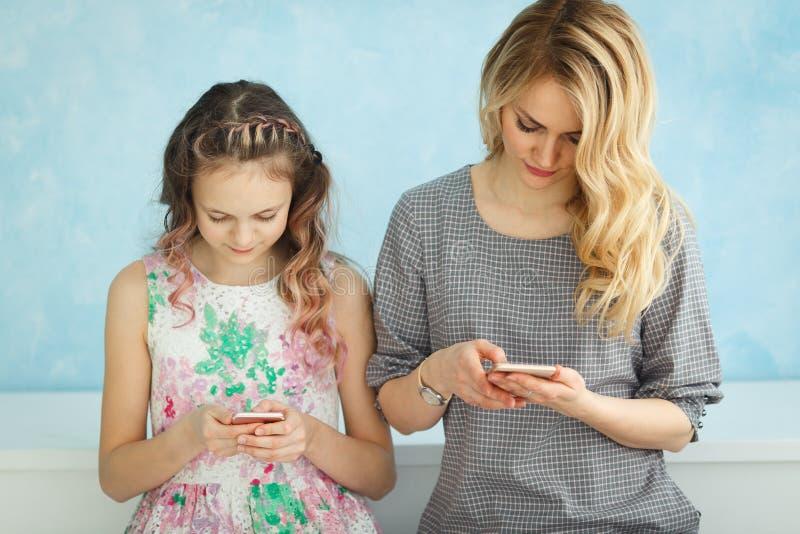 Matka i córka siedzimy obok each inny patrzeć w ich telefonach i no opowiadamy fotografia stock
