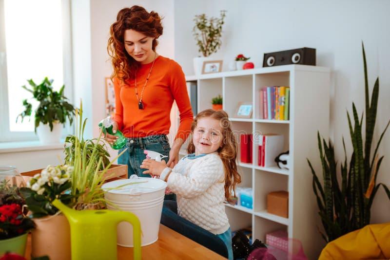 Matka i córka używa dyfuzory nawadnia do domu rośliny obrazy royalty free