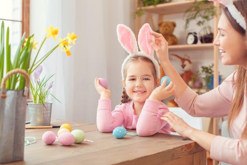 Matka i córka w królików ucho Easter świętowaniu siedzi dziewczyny mienia jajka wpólnie w domu obraz stock