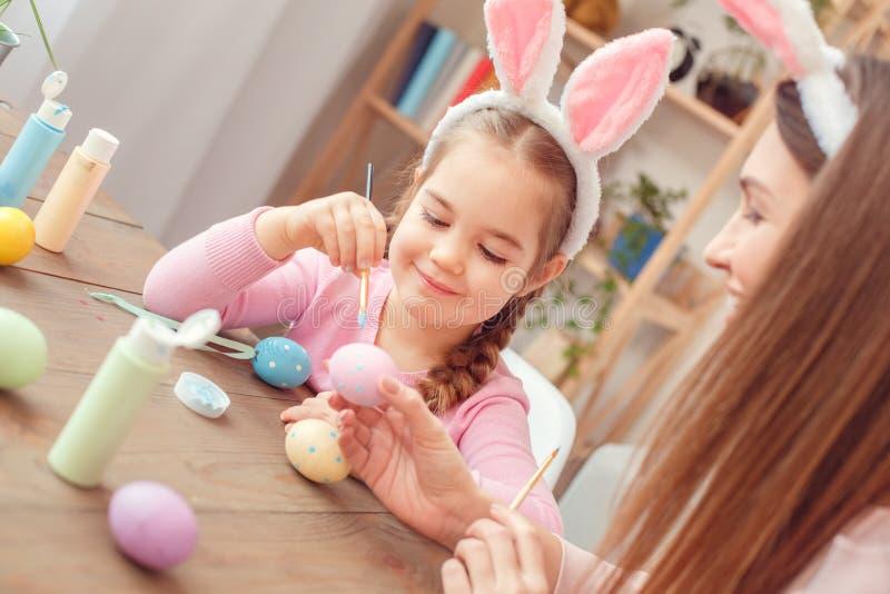Matka i córka w królików ucho Easter świętowaniu siedzi dziewczyny robi kropkom z szczotkarski radosnym wpólnie w domu zdjęcie stock