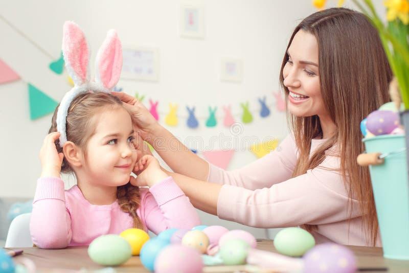 Matka i córka w królików ucho Easter świętowaniu siedzi mamy wzruszającego bazel wpólnie w domu obraz royalty free