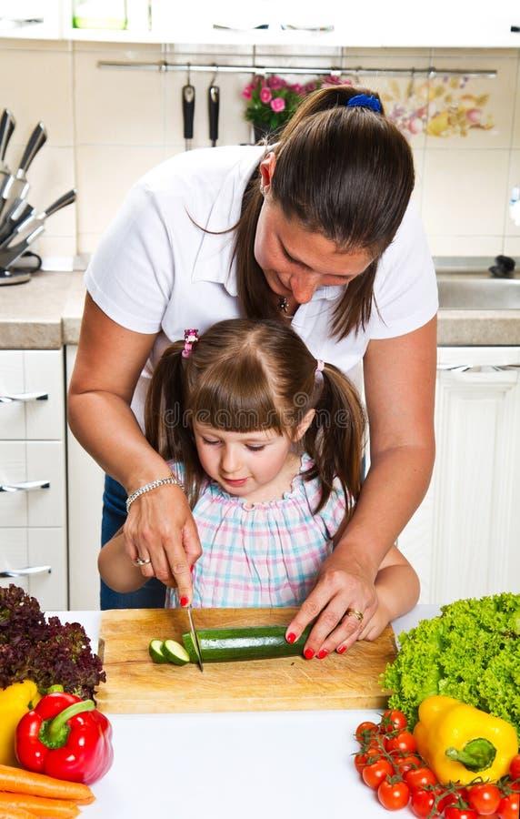 Matka i córka w kuchennych narządzań warzywach zdjęcie royalty free