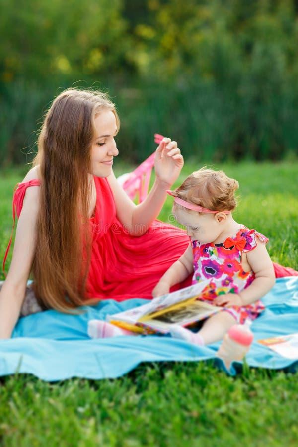 Matka i córka w parkowym obsiadaniu na dywanik czytelniczej książce fotografia royalty free