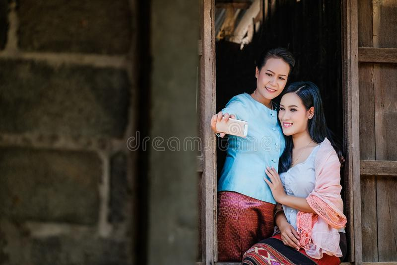 Matka i córka w tradycyjnej Tajlandzkiej sukni bierzemy obrazki one z telefonem komórkowym od drewnianego okno fotografia stock