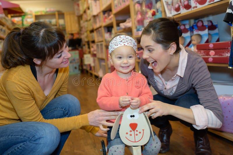 Matka i córka z atrakcyjnym sprzedawcą w zabawkarskim sklepie fotografia stock