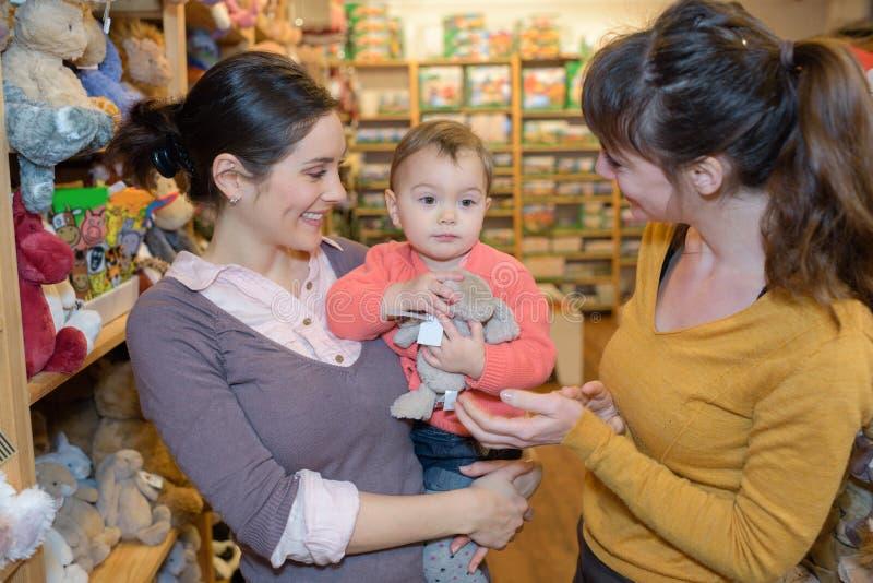 Matka i córka z atrakcyjnym sprzedawcą w zabawkarskim sklepie obraz royalty free