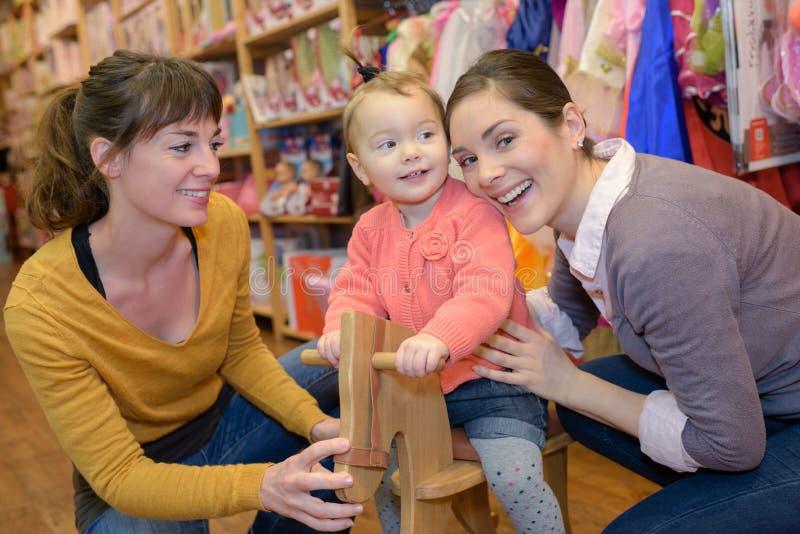 Matka i córka z atrakcyjnym sprzedawcą w zabawkarskim sklepie zdjęcie royalty free
