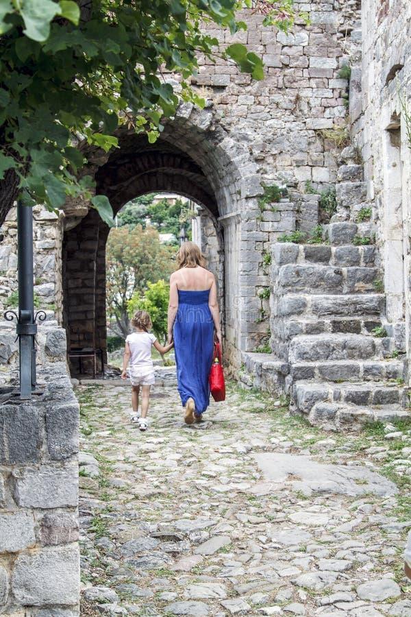 Matka i c?rka chodzimy w?r?d ruin stary miasteczko w Budv obraz royalty free