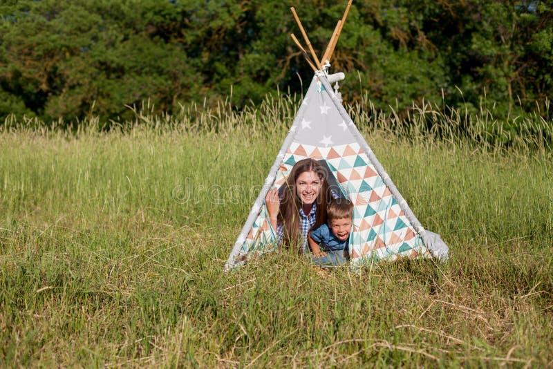 Matka i chłopiec na pinkinie przy namiotami obraz royalty free