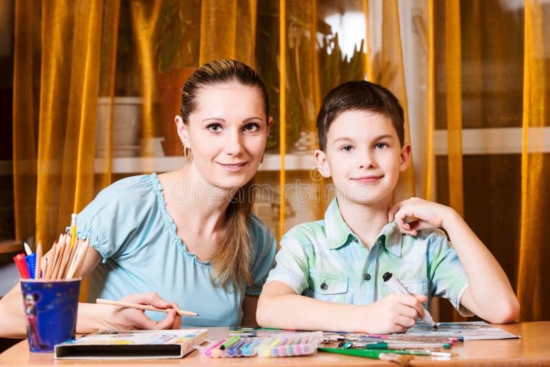 Matka i chłopiec robi pracie domowej wpólnie obrazy stock