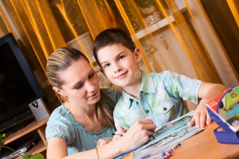 Matka i chłopiec robi pracie domowej wpólnie wędkującej fotografia stock