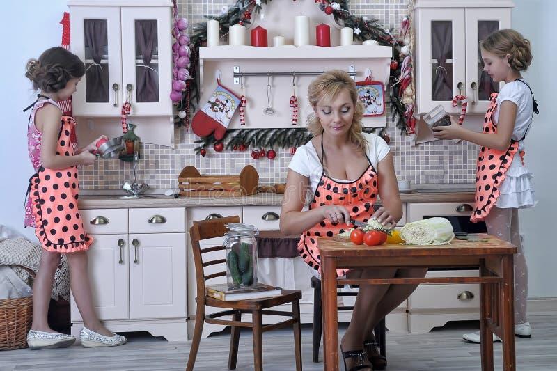 Matka i dwa córki w kuchni obraz stock