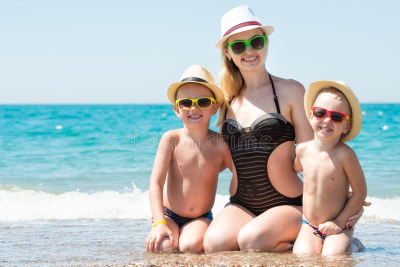 Matka i dwa syna w kapeluszach siedzi na plaży Lato rodzinny wakacje zdjęcie stock