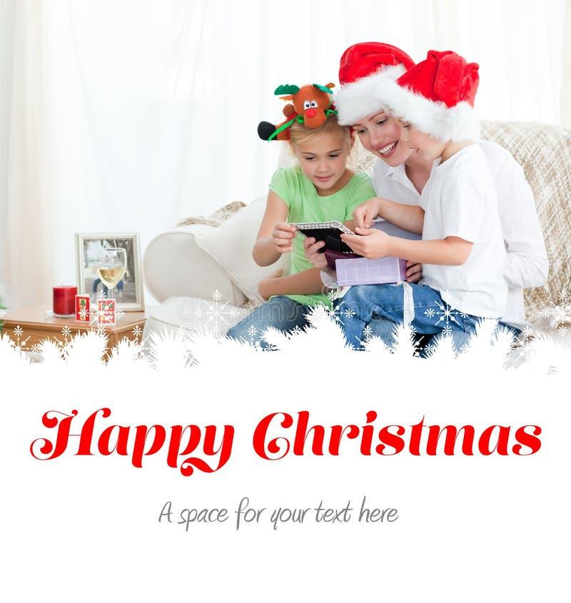 Matka i dzieci patrzeje kalendarzowego obsiadanie na kanapie obraz royalty free