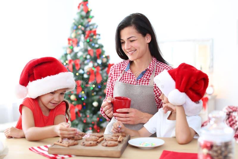 Matka i dzieci robi Bożenarodzeniowym ciastkom obraz stock