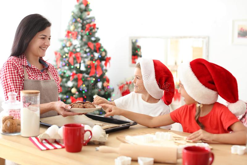 Matka i dzieci robi Bożenarodzeniowym ciastkom zdjęcia royalty free