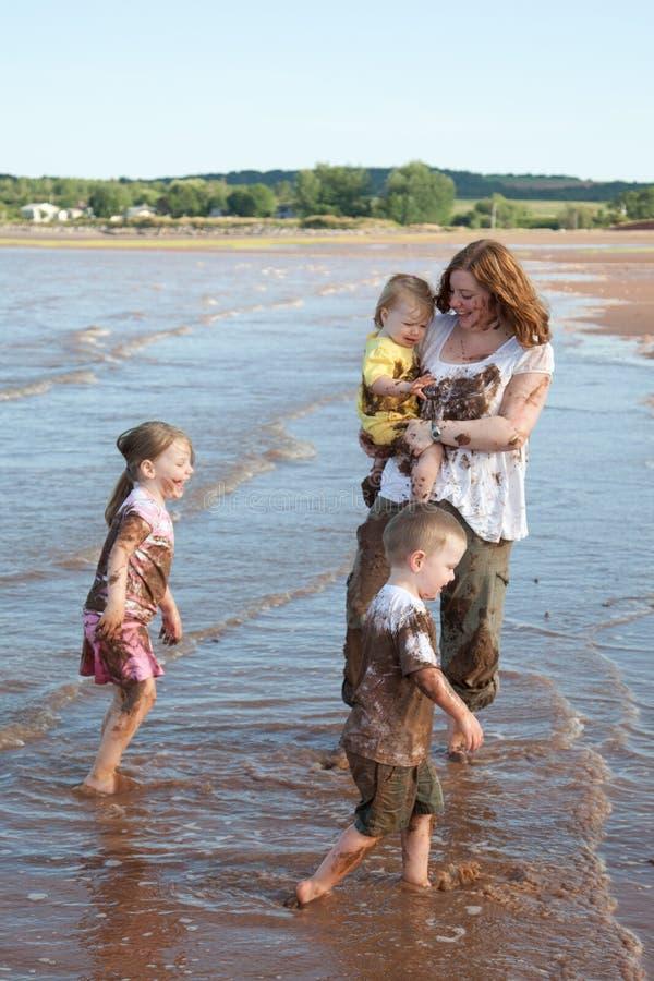 Matka i dzieciaki bawić się w błocie zdjęcie royalty free
