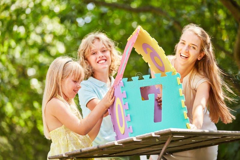 Matka i dzieciaki buduje łamigłówkę mamy zabawę w domu zdjęcia royalty free