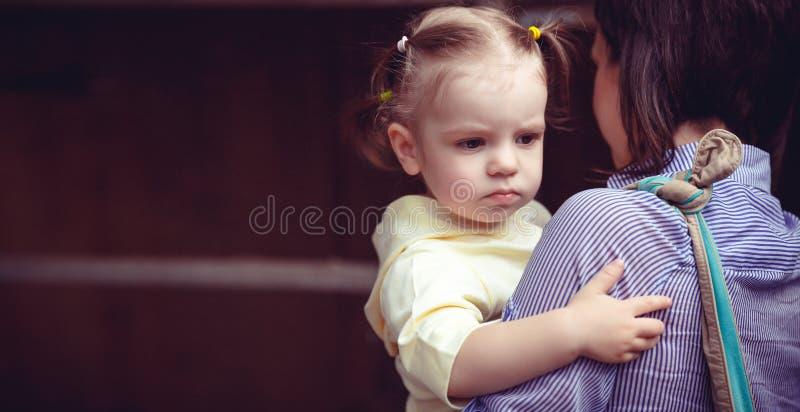 Matka i dziecko, śliczna mała dziewczynka odpoczywa na jej macierzystym ` s ramieniu, rocznika filtra skutek fotografia royalty free