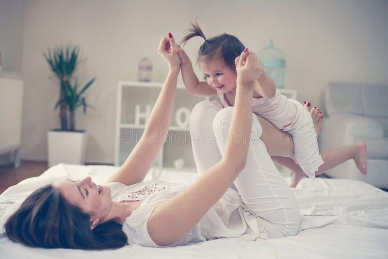 Matka i dziecko bawić się w łóżku obraz royalty free