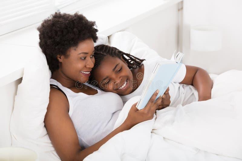 Matka I dziecko Czyta książkę W łóżku obrazy stock