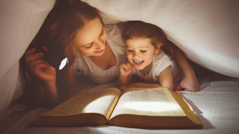 Matka i dziecko czytamy książkę pod koc z latarką zdjęcia royalty free