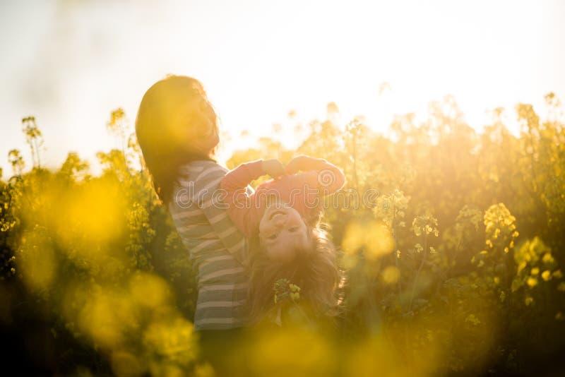 Matka i dziecko ma zabawę w rapeseed polu zdjęcia stock