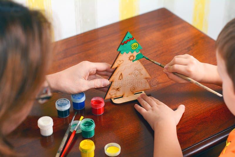Matka i dziecko malujemy drewnianej nowego roku ` s choinki Chłopiec i matka rysujemy nowego roku drzewa obraz stock