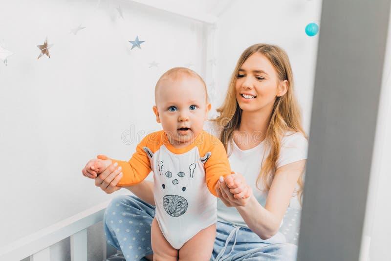 Matka i dziecko na białym łóżku Mama i dziecko bawią się Rodzic i małe dziecko spoczywają w domu Rodzina jest zabawna obrazy royalty free