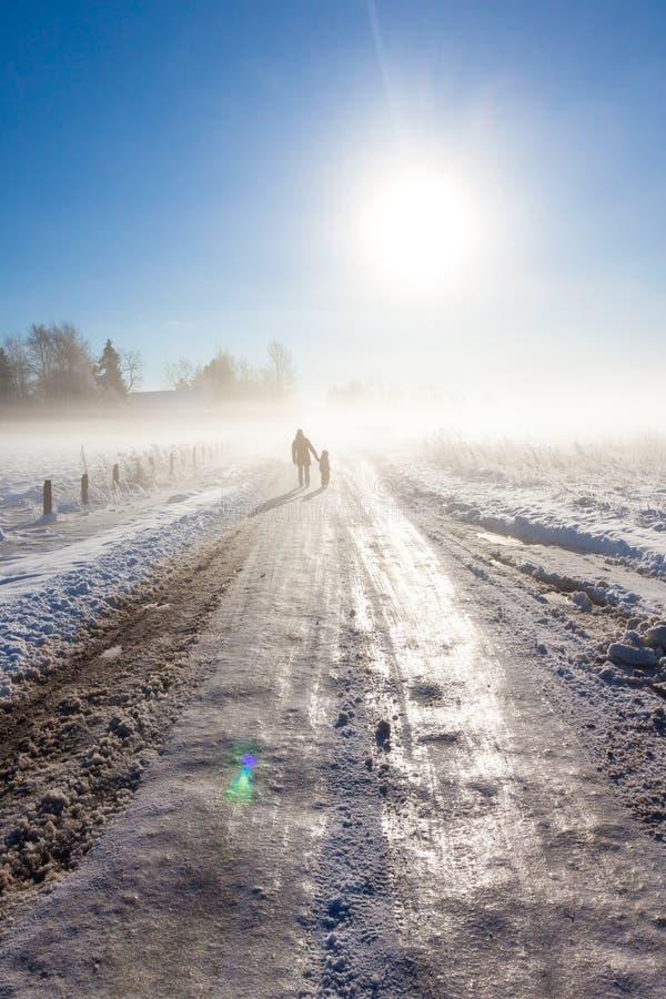 Matka i dziecko na mgłowej śnieżnej drodze zdjęcie royalty free