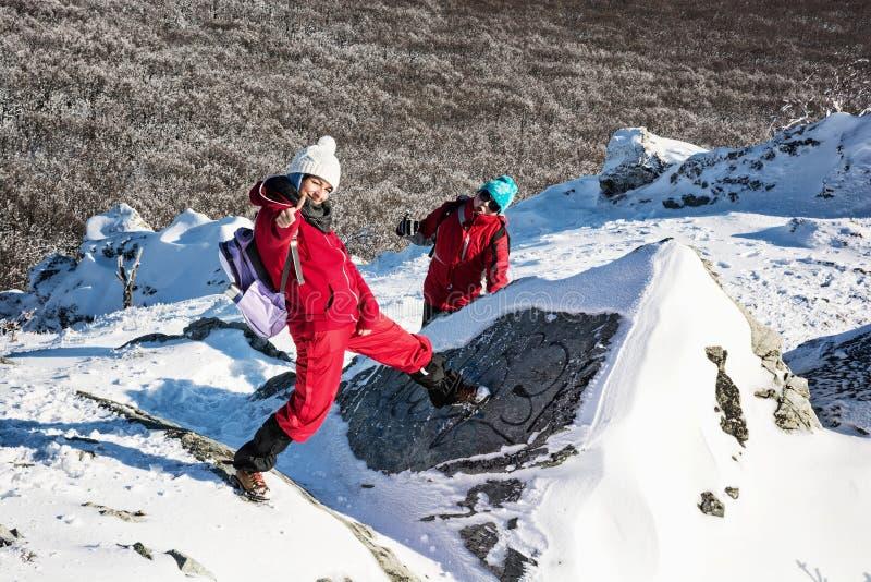 Matka i dziecko robi szalonym pozom na śnieżnych skałach, zima t obraz royalty free