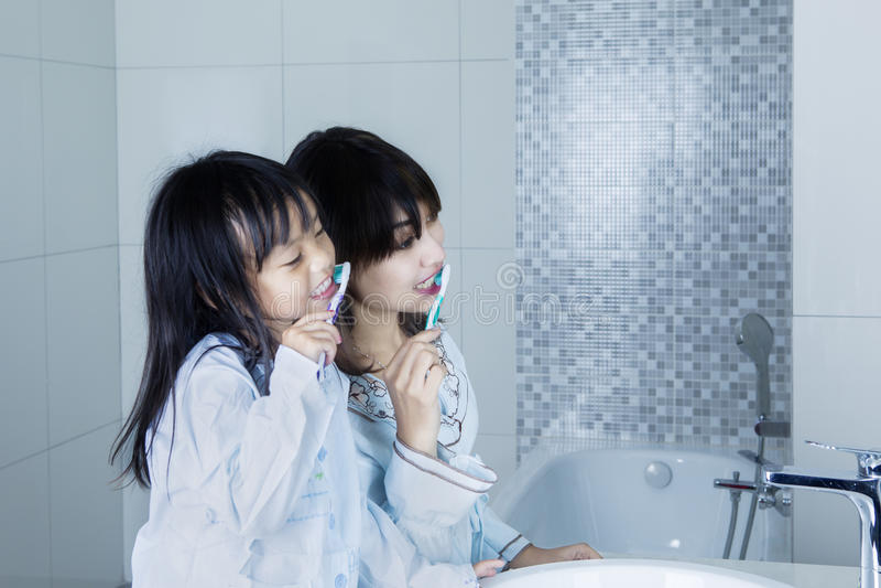 Matka i dziecko szczotkuje zęby wpólnie zdjęcie royalty free
