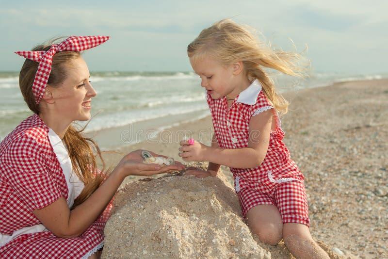 Matka i jej córka bawią się na plaży obrazy stock