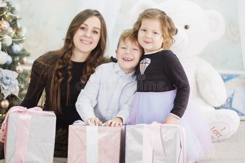 Matka i jej dwa ma?ego dziecka z Bo?enarodzeniowymi prezent?w pude?kami Rodzina na wigilii Matka i ma?e dzieci otwiera Xmas zdjęcia stock