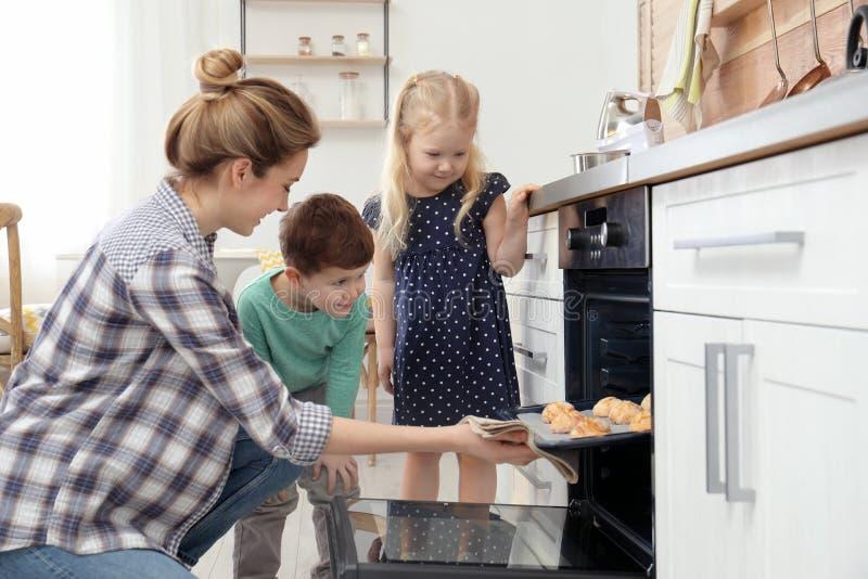 Matka i jej dzieci bierze za ciastkach od piekarnika obraz royalty free