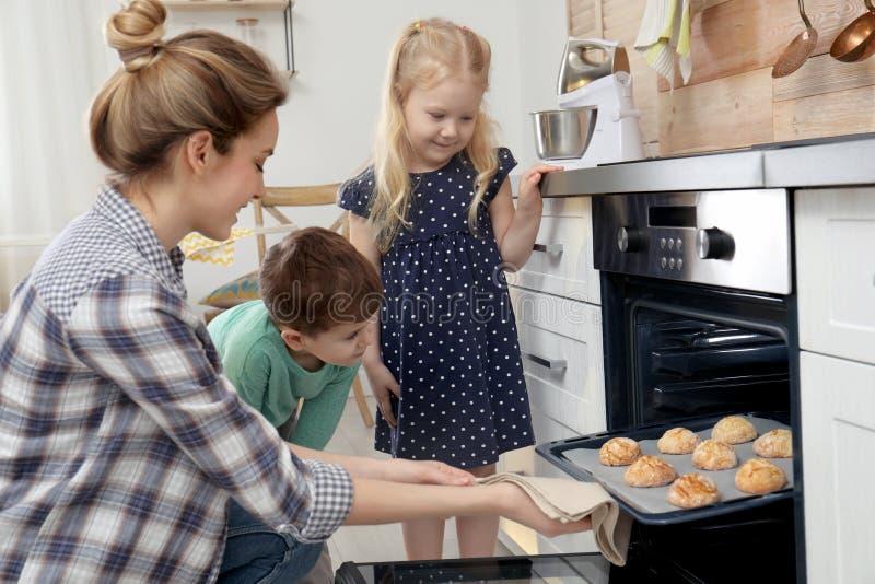 Matka i jej dzieci bierze za ciastkach od piekarnika zdjęcia stock