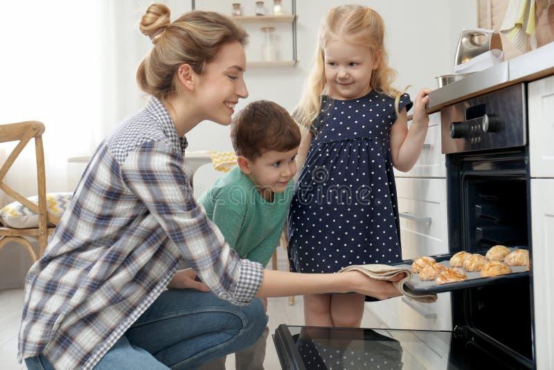 Matka i jej dzieci bierze za ciastkach od piekarnika zdjęcie royalty free