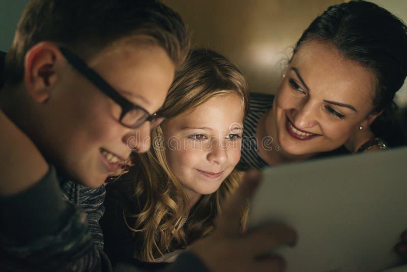Matka i jej dzieci z cyfrową pastylką zdjęcia stock