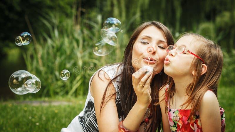 Matka i mała dziewczynka dmucha mydlanych bąble w parku obrazy stock